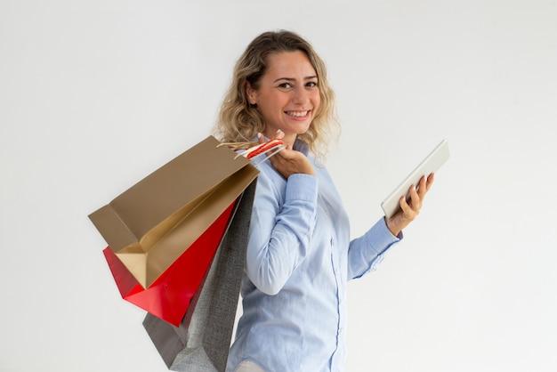 Lächelnde optimistische frau, die tablette für das on-line-einkaufen verwendet