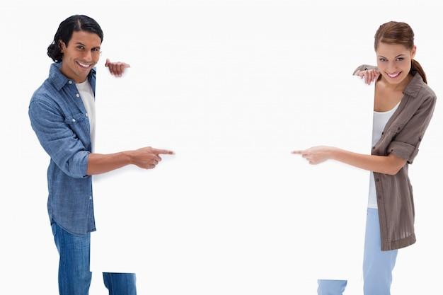 Lächelnde paare, die auf leeres zeigen, unterzeichnen herein ihre hände