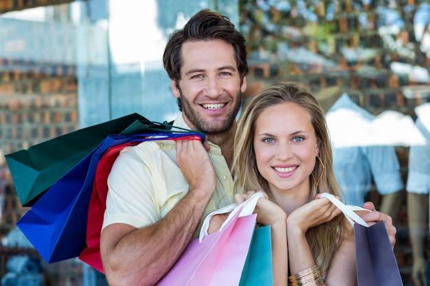 Lächelnde paare, die einkaufstaschen halten