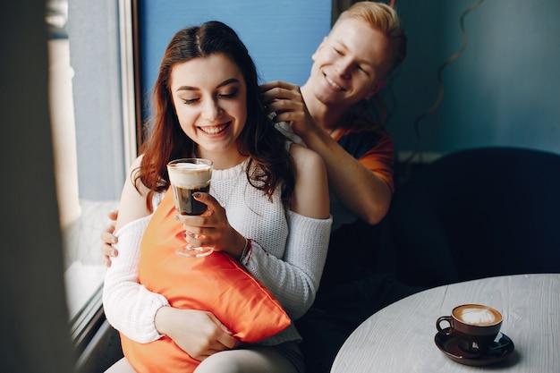 Lächelnde paare, die in einem café sitzen und einen kaffee trinken