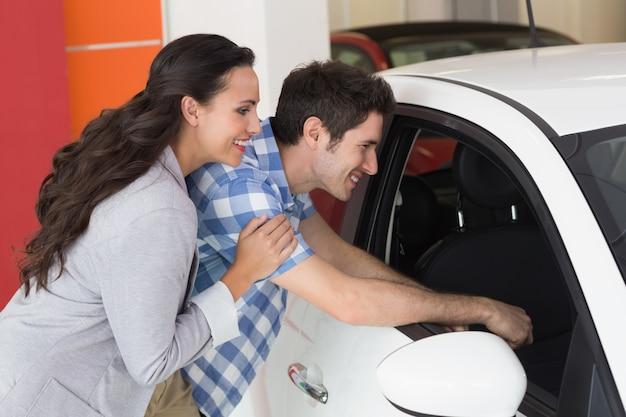 Lächelnde paare, die innerhalb eines autos schauen