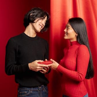 Lächelnde paare, die mit geschenk für chinesisches neues jahr aufwerfen