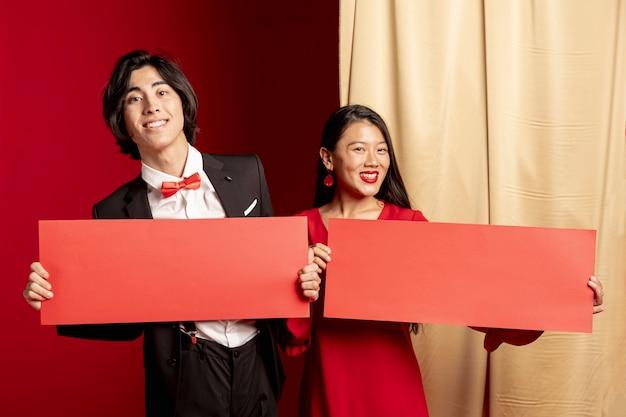 Lächelnde paare, die mit roten umschlägen für chinesisches neues jahr aufwerfen