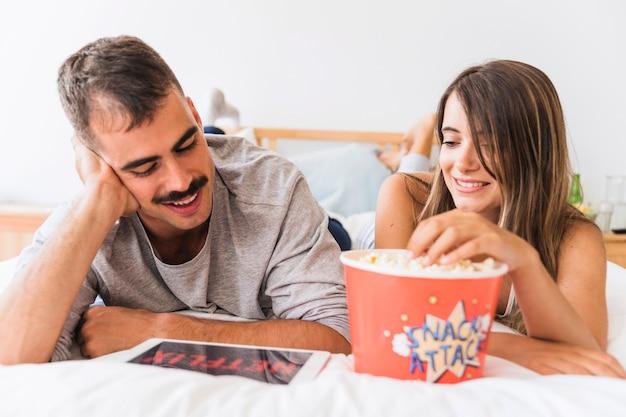 Lächelnde paare, die popcorn- und netflix-reihe genießen