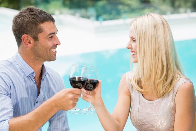 Lächelnde paare, die rotwein beim sitzen durch swimmingpool rösten