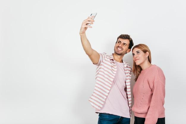 Lächelnde paare, die selfie am telefon nehmen