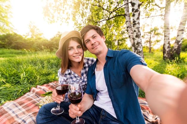 Lächelnde paare, die selfie auf picknick nehmen