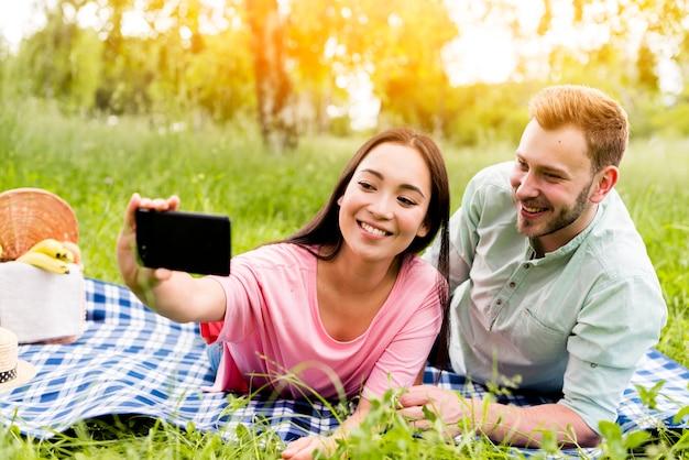 Lächelnde paare, die selfie im park nehmen