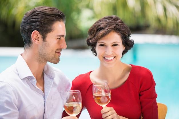 Lächelnde paare, die weißwein halten