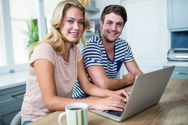 Lächelnde paare, die zu hause auf laptop schreiben