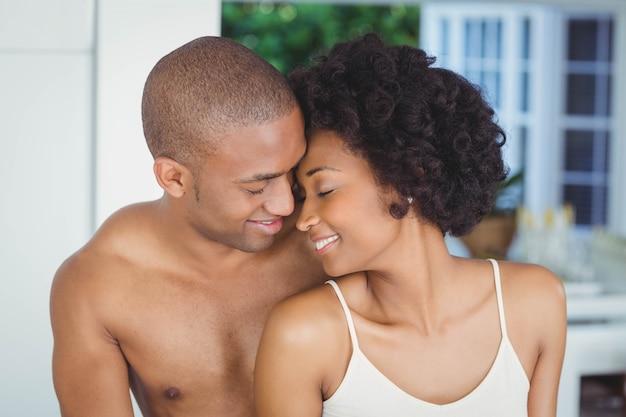 Lächelnde paare, die zu hause mit geschlossenen augen umarmen