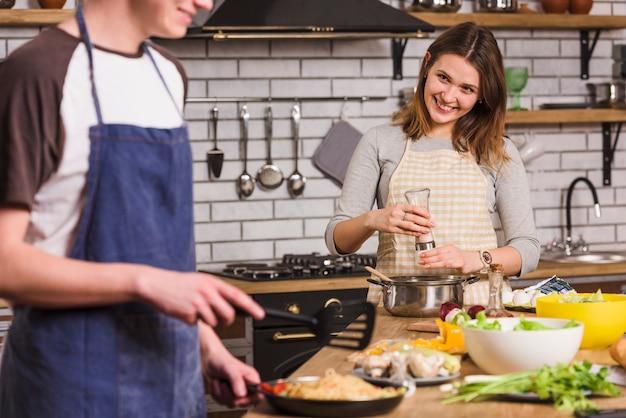 Lächelnde paare, die zusammen gerichte kochen