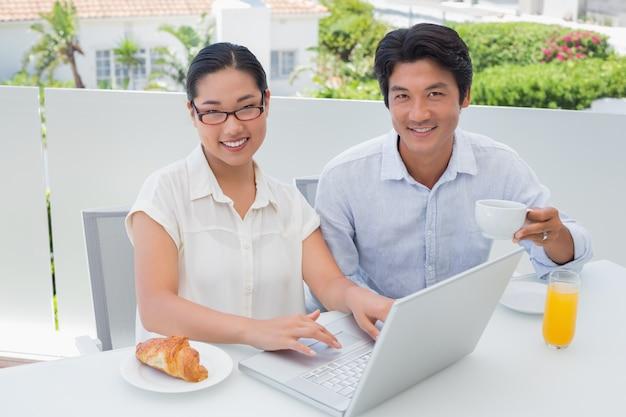 Lächelnde paare, die zusammen unter verwendung des laptops frühstücken