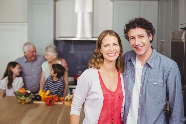 Lächelnde paare mit familie in der küche
