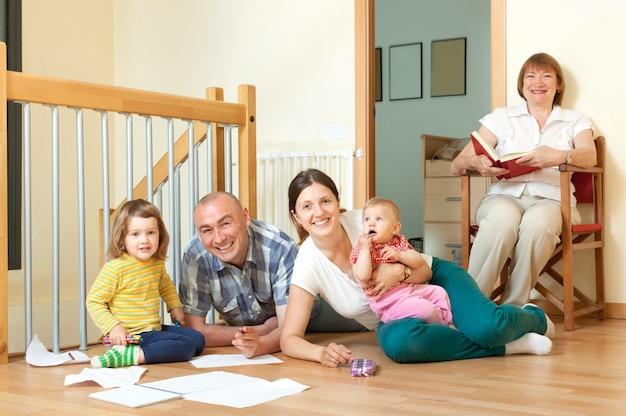 Lächelnde paare mit ihrer nachkommenschaft und großmutter auf boden zu hause im wohnzimmer