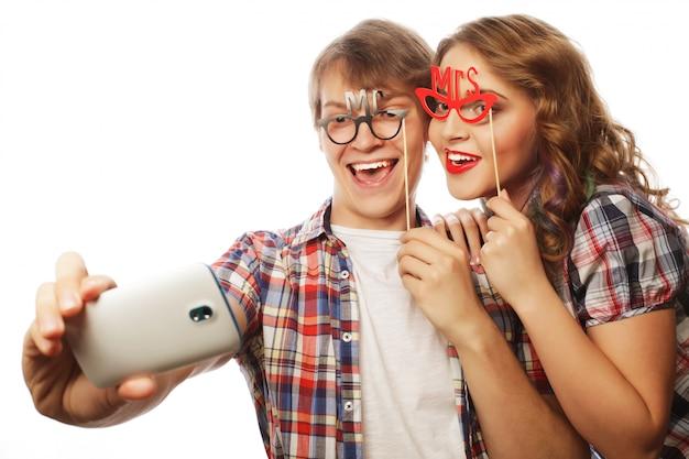 Lächelnde paare mit smartphone, selfie und spaß.