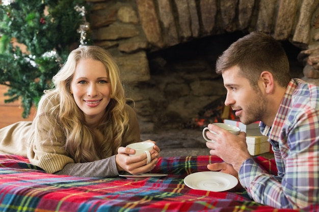 Lächelnde paare mit teetassen vor beleuchtetem kamin