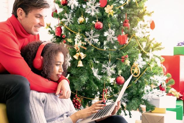 Lächelnde paare sitzen auf dem sofa, das online mit laptop im gemütlichen raum kauft.