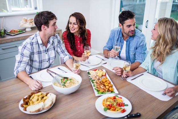 Lächelnde paarfreunde, die zusammen zu hause essen