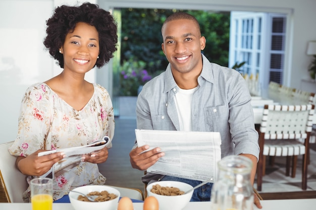 Lächelnde paarlesezeitschrift und -dokumente während des frühstücks in der küche