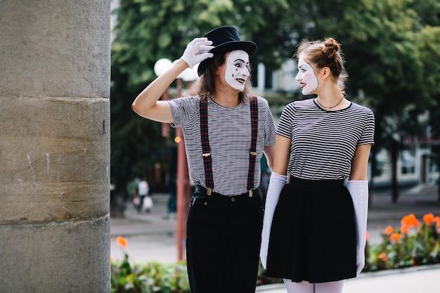 Lächelnde pantomimepaare, die einander betrachten