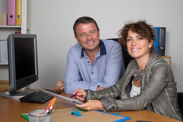 Lächelnde partner, die am schreibtisch mit laptop im büro arbeiten