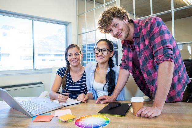 Lächelnde partner, die zusammen an laptop und analog-digital wandler arbeiten