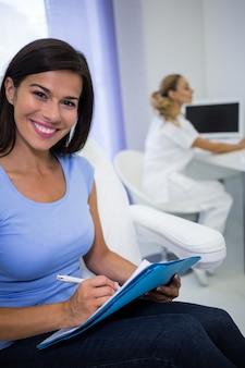 Lächelnde patientin, die auf eine medizinische akte schreibt