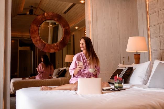 Lächelnde perfekte frau im rosa bademantel mit sitzendem bett der tasse tee / des kaffees und des laptops im gemütlichen hotelzimmer.