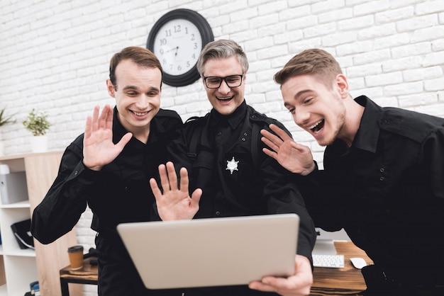 Lächelnde polizeibeamten starren auf laptop an.