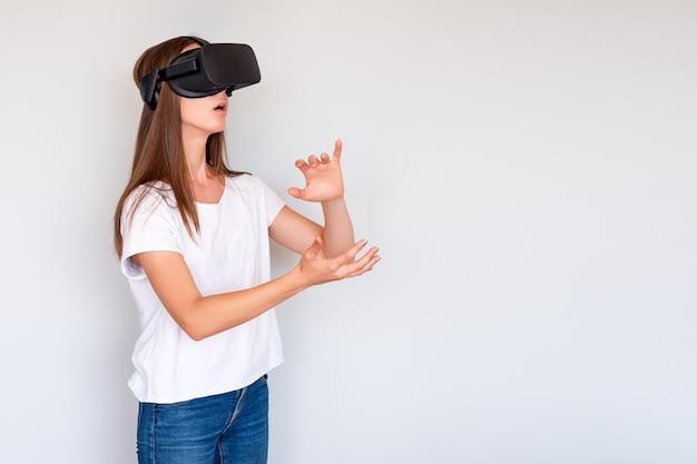 Lächelnde positive frau, die virtual-reality-brillen-headset trägt, vr-box. verbindung, technologie, neue generation, fortschrittskonzept. mädchen, das versucht, objekte in der virtuellen realität zu berühren. studioaufnahme auf grau