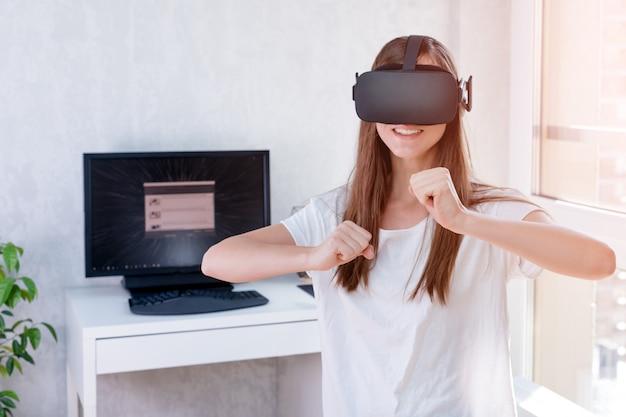 Lächelnde positive frau, die virtual-reality-brillen-headset trägt, vr-box. verbindung, technologie, neue generation, fortschrittskonzept. mädchen, das versucht, objekte in der virtuellen realität zu berühren
