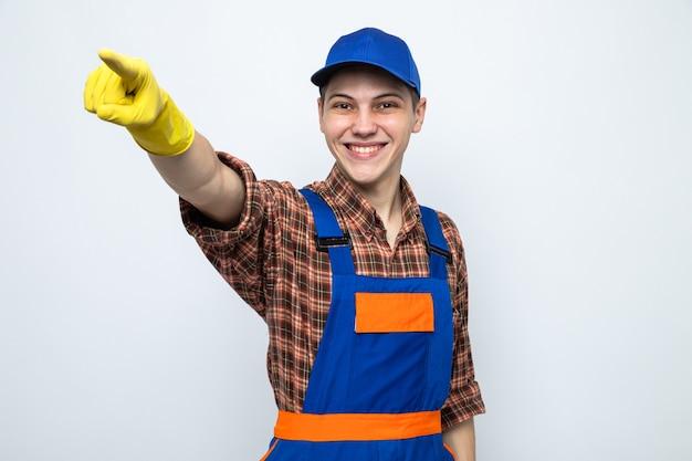 Lächelnde punkte an der seite junger putzmann, der uniform und mütze mit handschuhen trägt