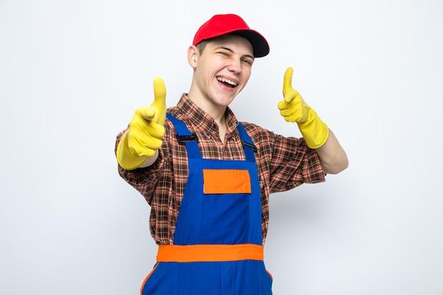 Lächelnde punkte an der vorderseite junger putzmann in uniform und mütze mit handschuhen