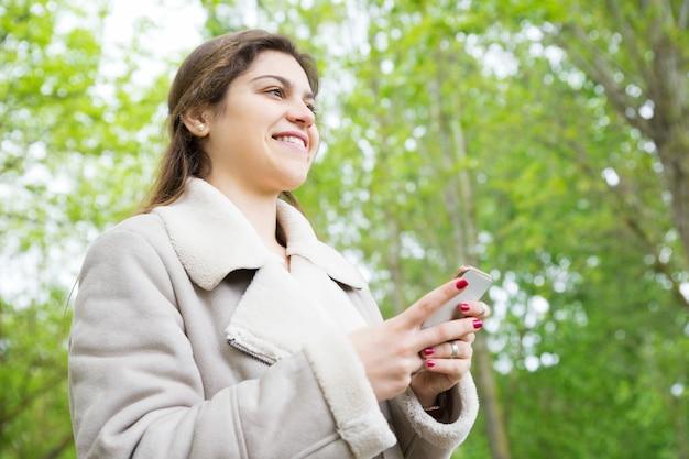Lächelnde recht junge frau, die smartphone im park verwendet