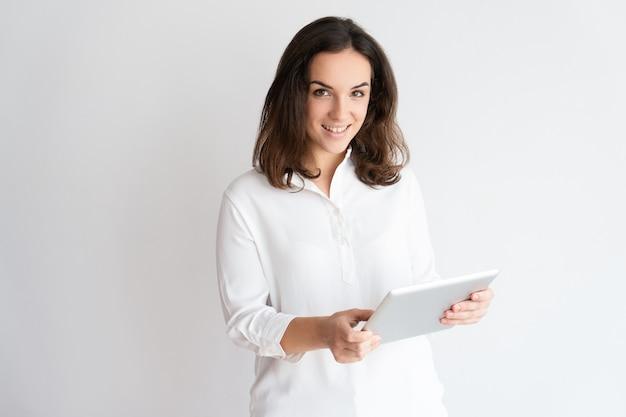 Lächelnde recht junge frau, die tablet-computer verwendet und kamera betrachtet.