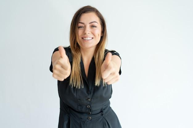 Lächelnde recht junge frau im schwarzen kleid, das thumbs-up beim ausdrücken ihrer zustimmung zeigt