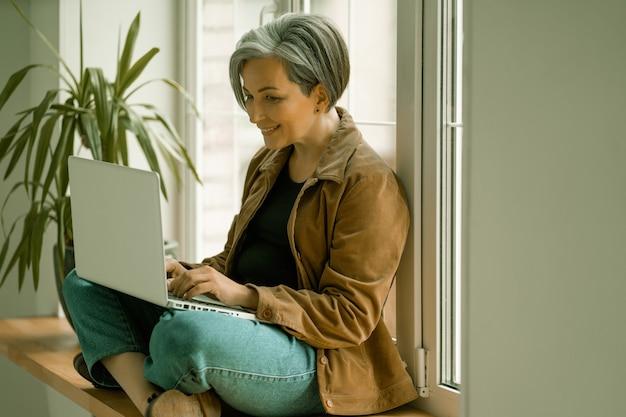 Lächelnde reife frau betrachtet webkamera, die am virtuellen video-chat teilnimmt oder mit computer arbeitet