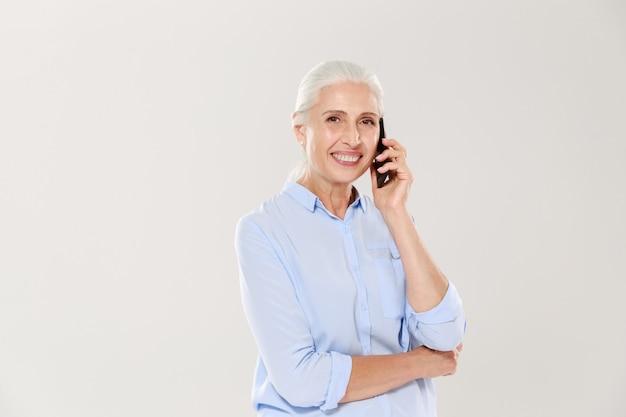 Lächelnde reife frau, die auf smartphone lokalisiert spricht