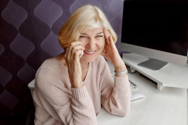 Lächelnde reife frau, die handy während der arbeit durch computer zu hause verwendet