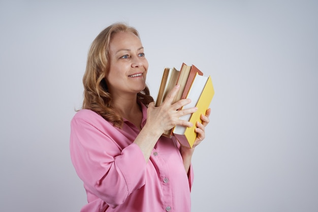 Lächelnde reife lehrerin im rosa hemd, die einen stapel bücher hält. bildungskonzept.