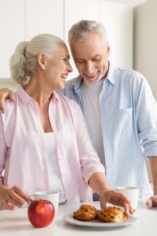Lächelnde reife liebespaarfamilie, die an der küche steht