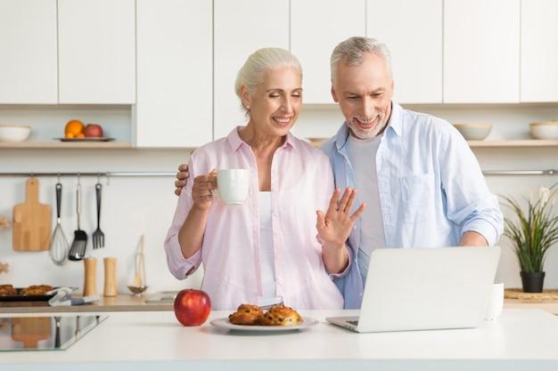 Lächelnde reife liebespaarfamilie, die gebäck isst, während laptop verwendet