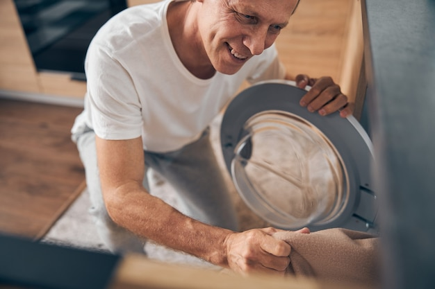 Lächelnde reife männliche person, die positivität ausdrückt, während sie gerne im haus arbeitet work
