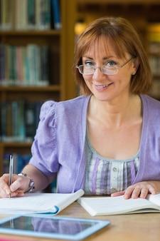 Lächelnde reife studentin am schreibtisch in der bibliothek