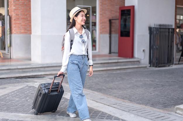 Lächelnde reisende, die schwarze koffergepäcktasche schleppt, die zum passagiereinstieg im flughafen geht, reisekonzept.
