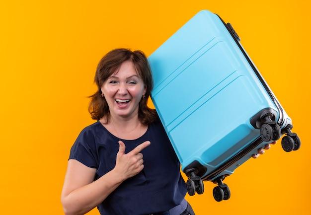 Lächelnde reisende frau mittleren alters hält und zeigt auf koffer auf