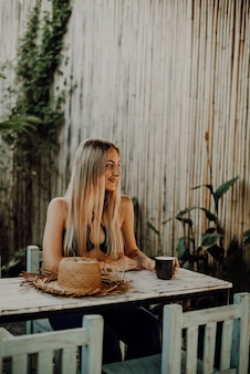 Lächelnde reisende sitzt am tisch, es ist ihr strohhut im café. hübsche frau hat eine gute zeit in ihrem urlaub in thailand.