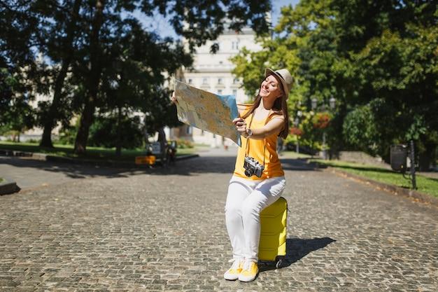 Lächelnde reisende touristische frau in gelber kleidung hut sitzt auf koffer auf der suche nach stadtplan-suchroute in der stadt im freien. mädchen, das ins ausland reist, um am wochenende zu reisen. tourismus reise lebensstil.