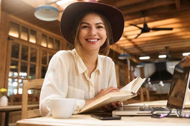 Lächelnde reizende frau im hut, die drinnen am kaffeetisch sitzt